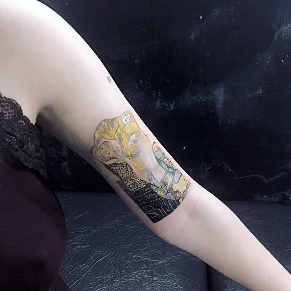 Klimt's 'Water Serpents I' inspired tattoo on the left bicep.