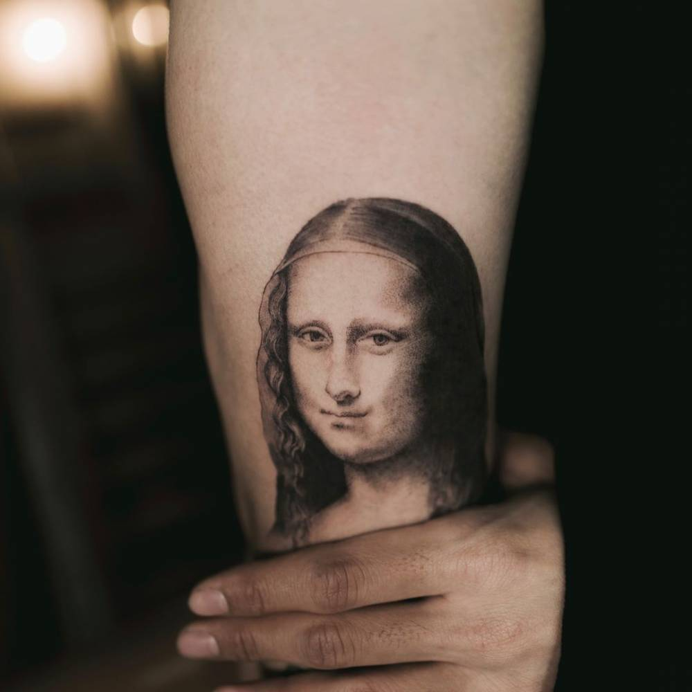 Fine line Mona Lisa tattoo on the right upper arm.