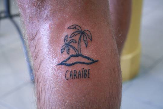"""Calf tattoo saying """"Caraïbe"""" together with an island and two palm trees."""