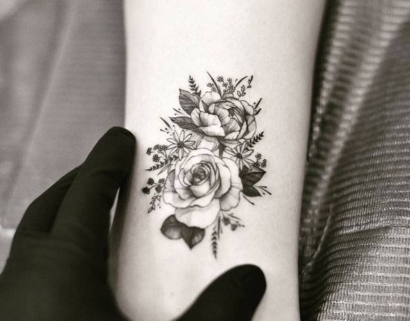 Peony and rose tattoo on the bicep.