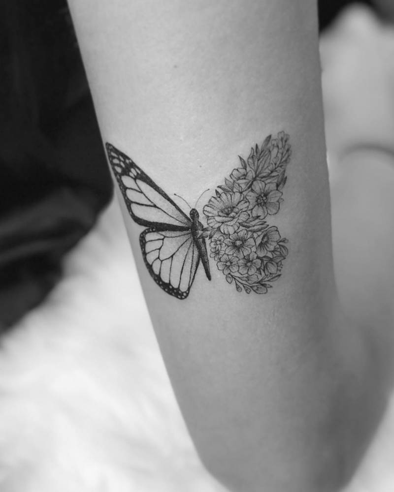 Flower butterfly tattoo on the back of the right arm.