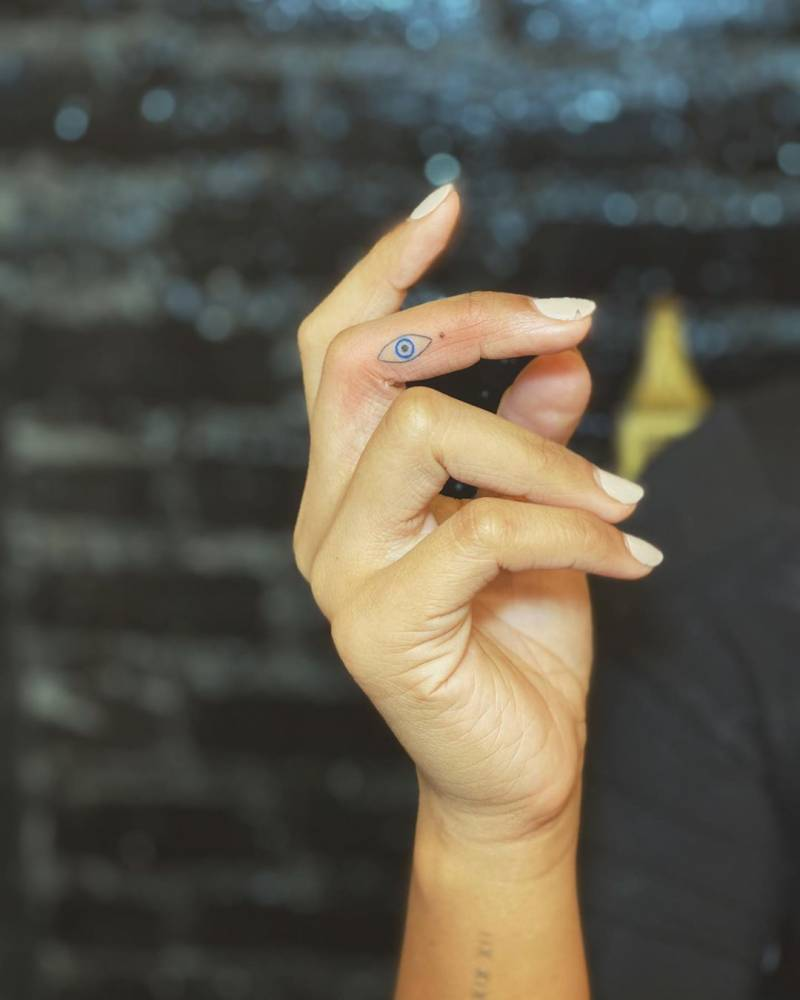 Evil eye tattoo on the right middle finger.