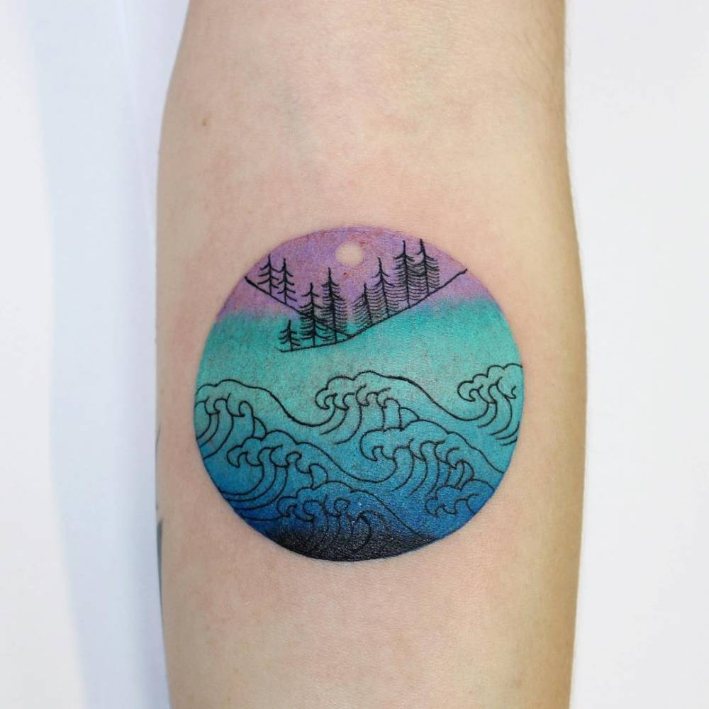 Abstract circle tattoo on the inner forearm.