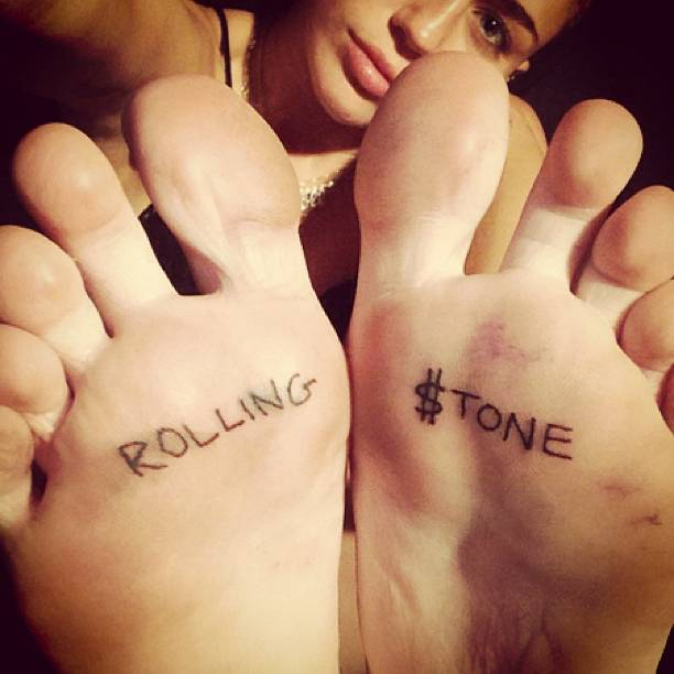 """Matching """"Rolling $tone"""" tattoos on the soles of Miley Cyrus' feet."""