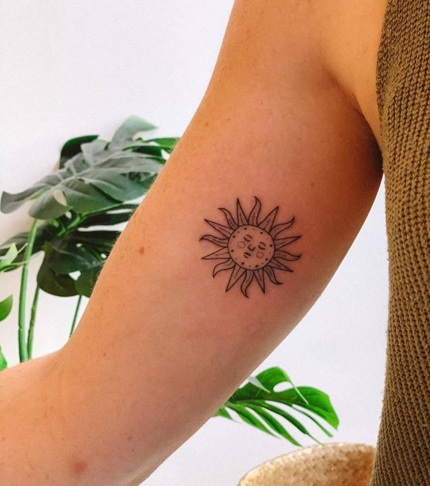 Sun tattoo on the inner arm.