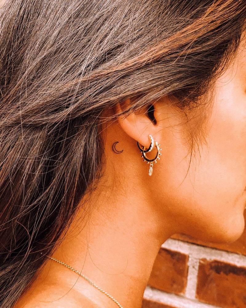 Crescent moon tattoo on the back of the right ear.