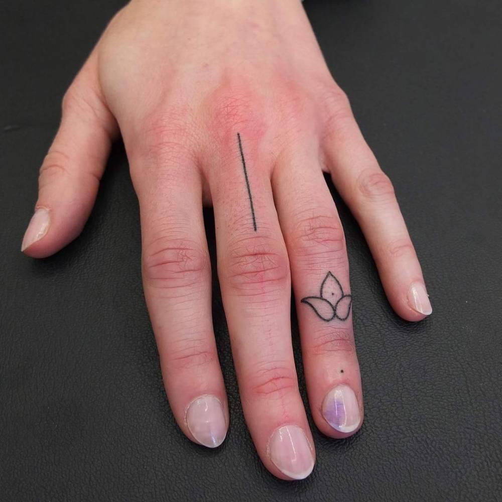 Hand poked minimalist finger tattoos.