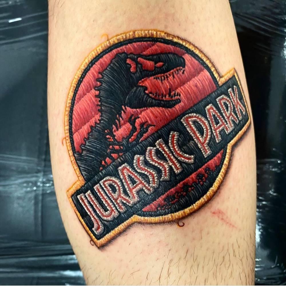 Jurassic Park tattoo on the calf.
