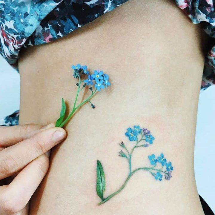 Forget-me-not flower tattoo on the left side of the hip.