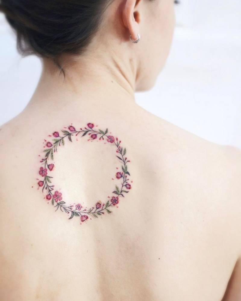 Cherry blossom flower wreath tattoo on the upper back.