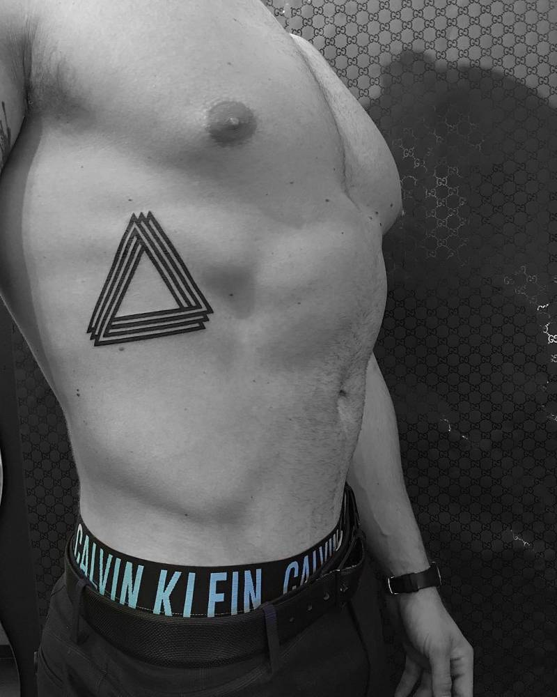 Impossible triangle tattoo on the right side ribcage.