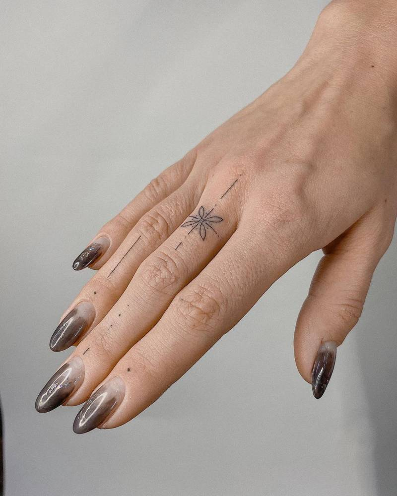 Ornamental hand-poked tattoo on fingers