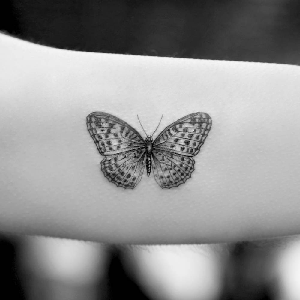 Single needle butterfly tattoo on the left inner arm.