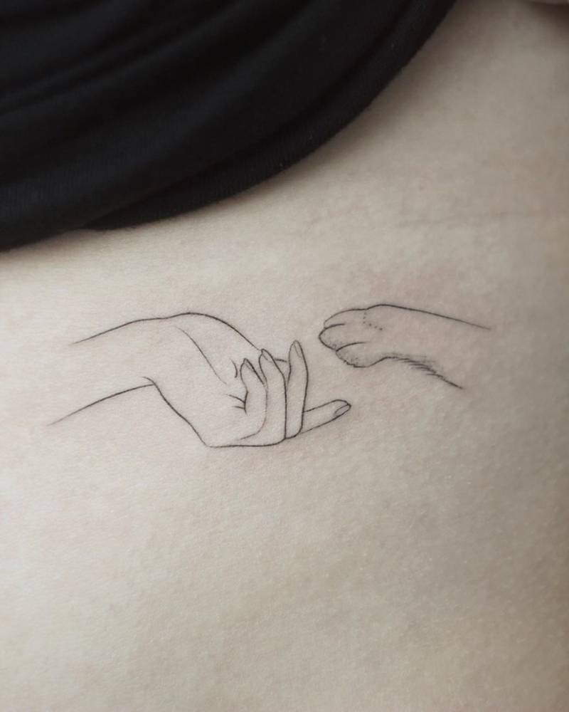 Fine line hand and paw tattoo on the rib