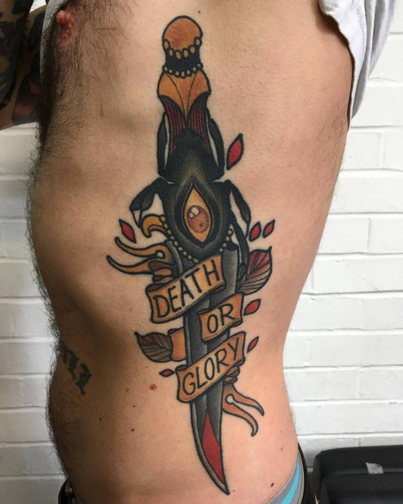 Healed neotraditional dagger tattoo on the left side.