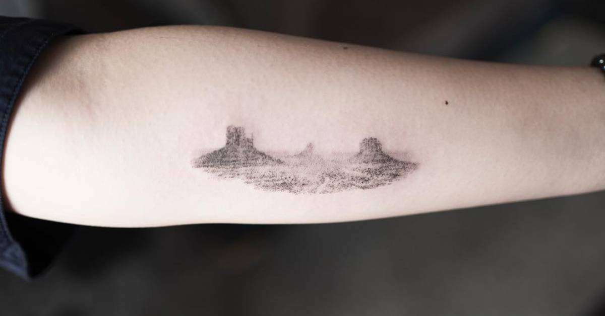 Monument valley tattoo on the left inner forearm for Single needle tattoo artists near me