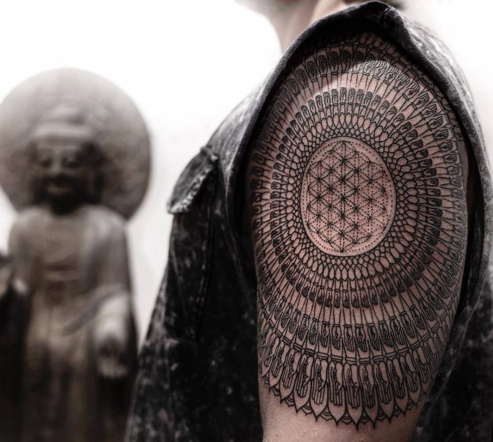 Thousand arms of compassion mandala tattoo on the upper arm