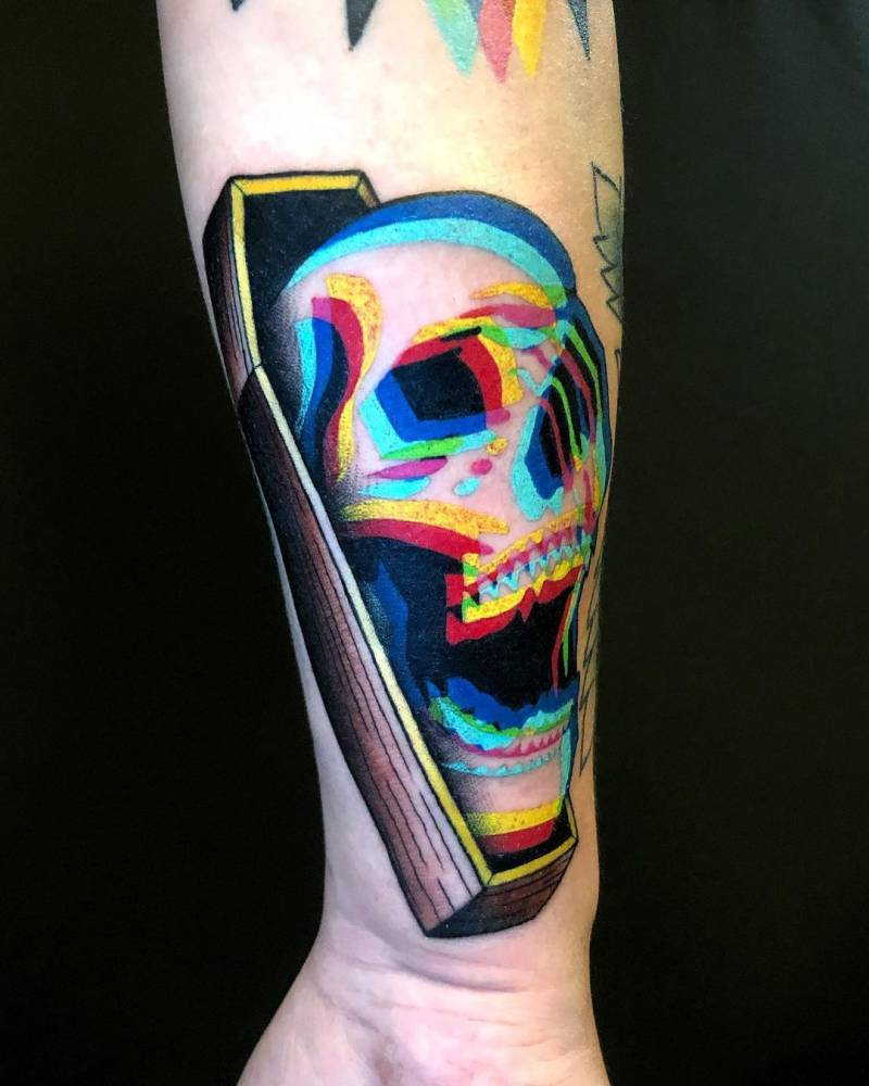 Anaglyph skull in a coffin tattooed on the forearm