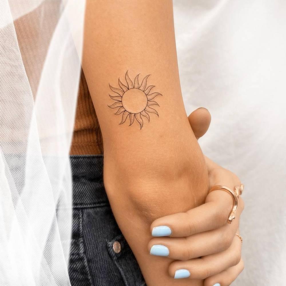Fine line sun tattoo on the tricep