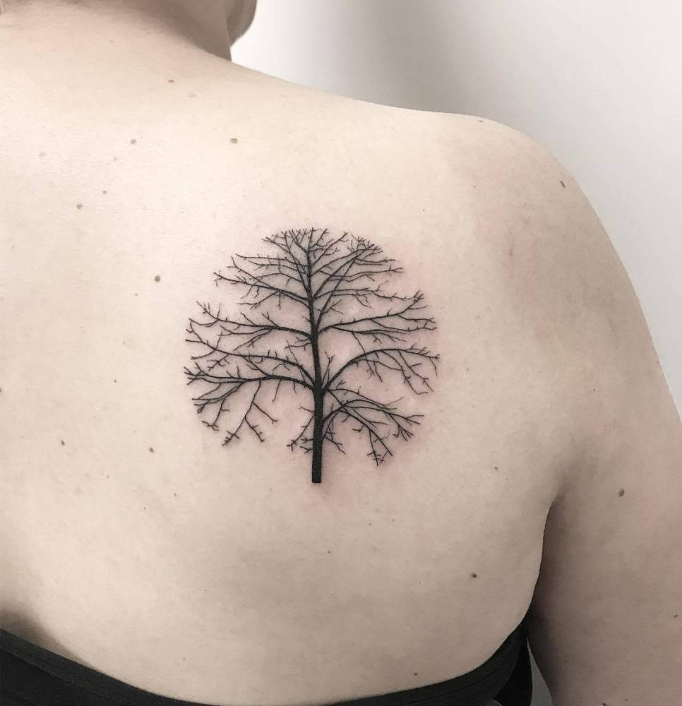 Circular tree tattoo on the right shoulder blade.