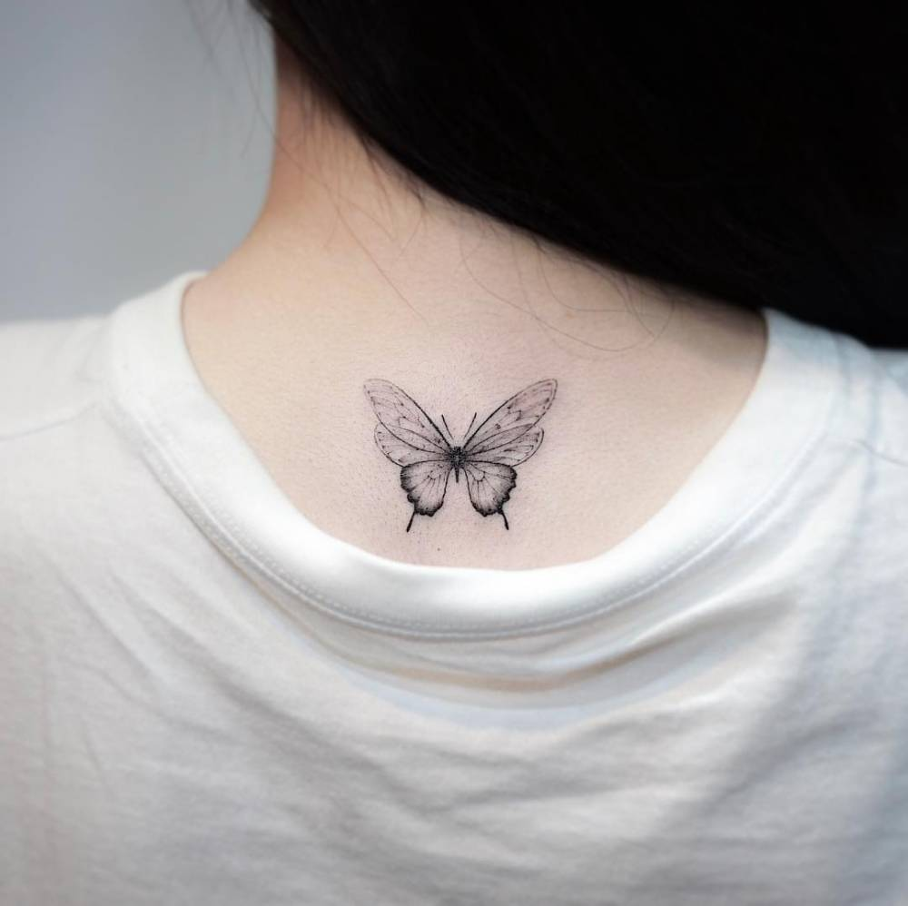 Fine line butterfly tattoo on the upper back