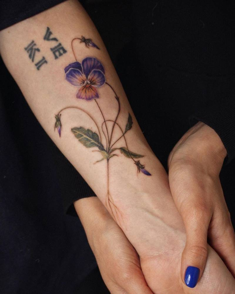Watercolor pansy tattoo on the inner forearm.