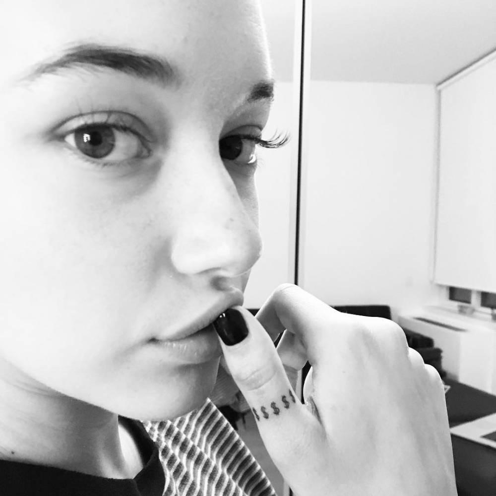 Dollar sign ring tattoo on Sarah Snyder's thumb finger.