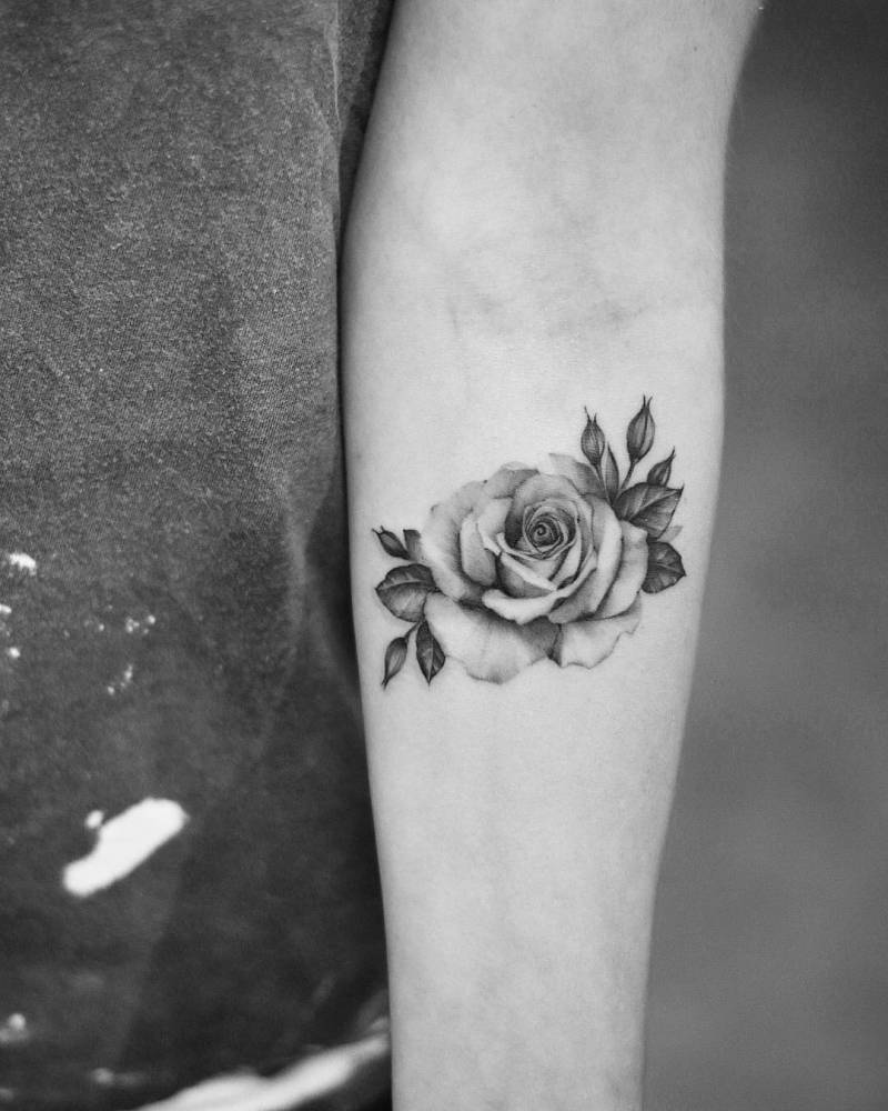 Single needle rose tattoo on the left inner forearm.