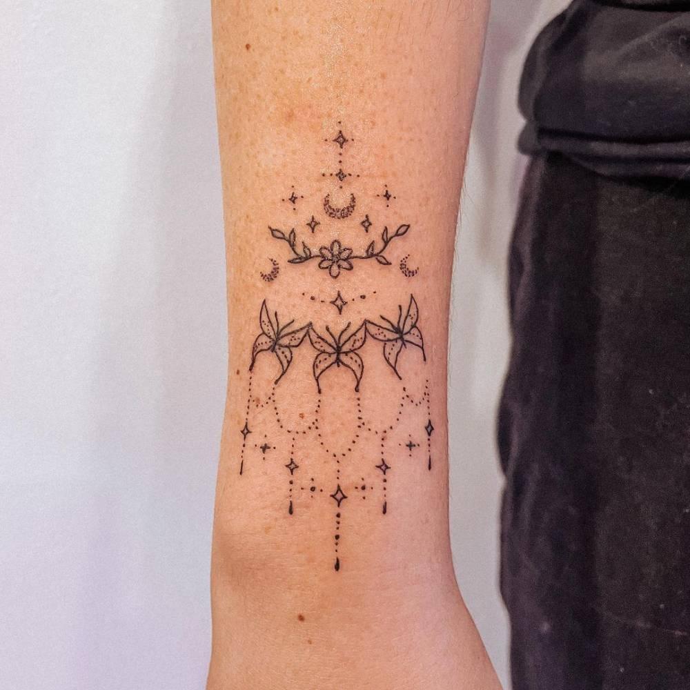 Fine line ornamental tattoo on the wrist.