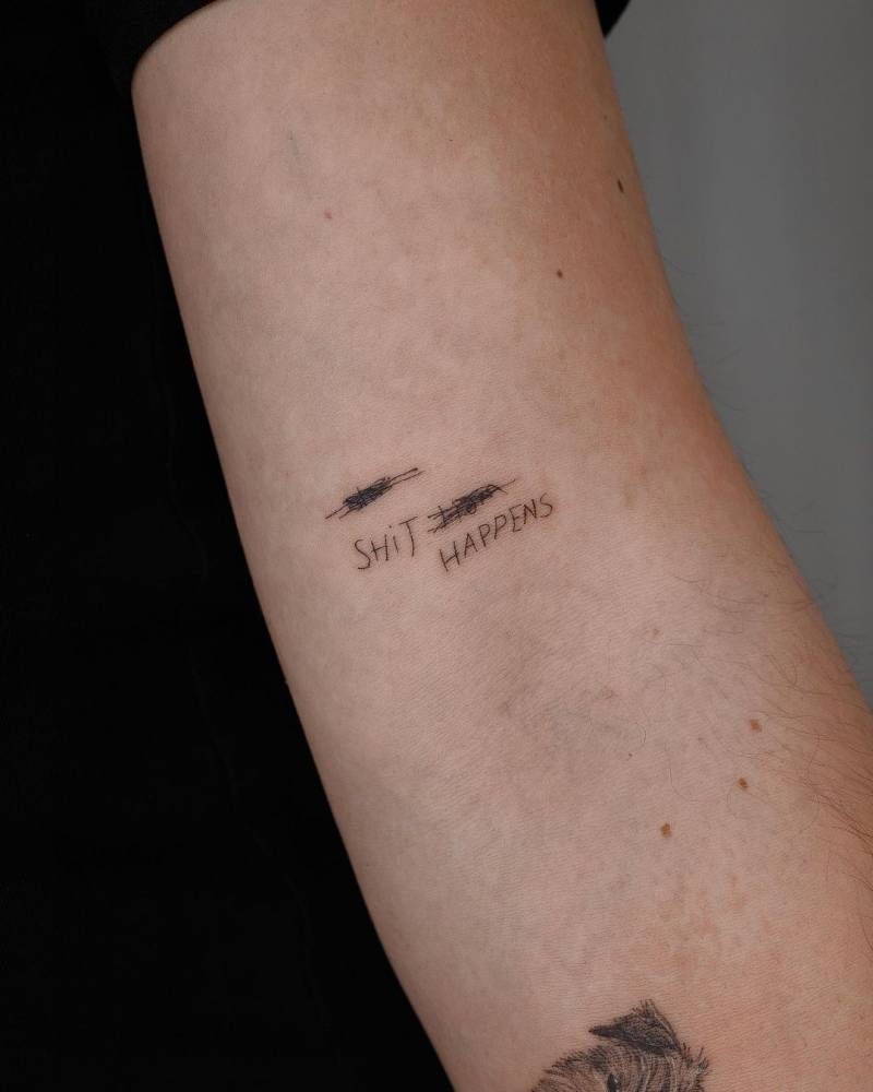"""""""Shit happens"""" lettering tattoo on the bicep."""