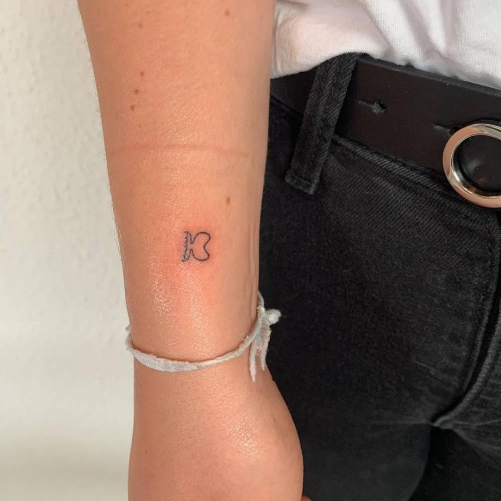 Minimalist fish tattoo on the wrist.