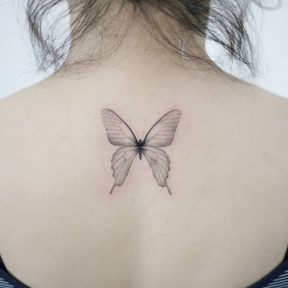 Single needle butterfly tattoos on the upper back.