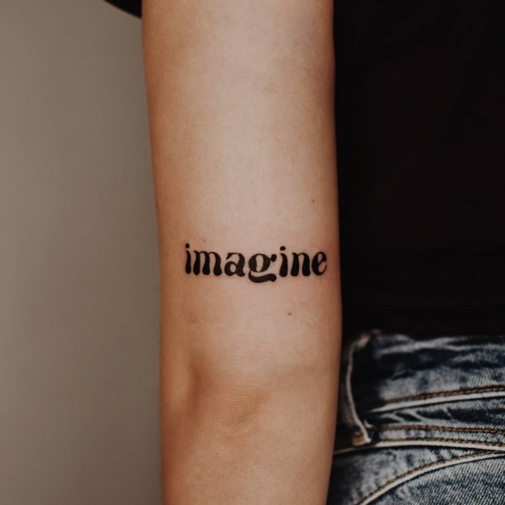 """Imagine"" lettering tattoo on the tricep."