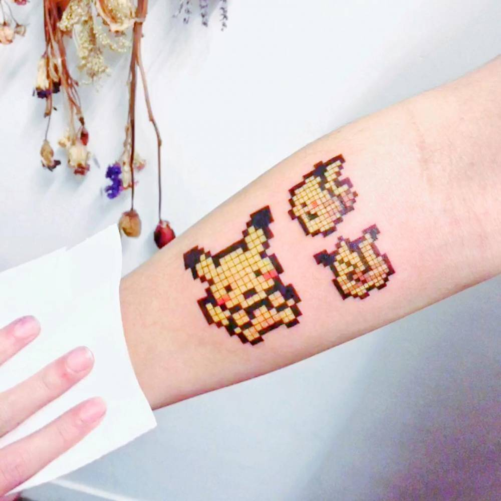 Pixelated Pikachu tattoo on the inner forearm.