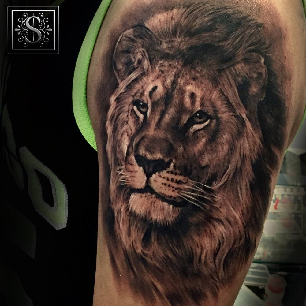 Black and grey style lion tattoo on the left forearm.