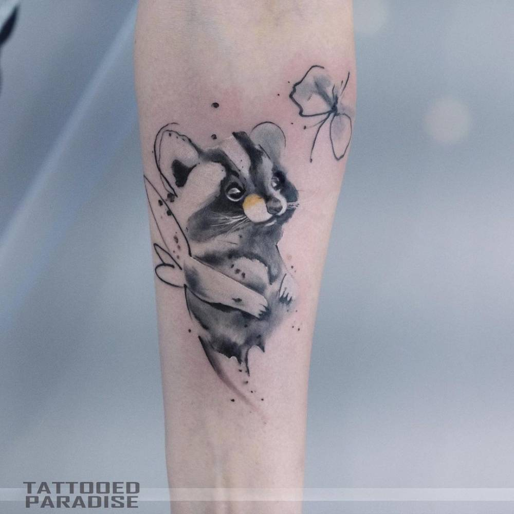 Watercolor raccoon tattoo on the inner forearm.