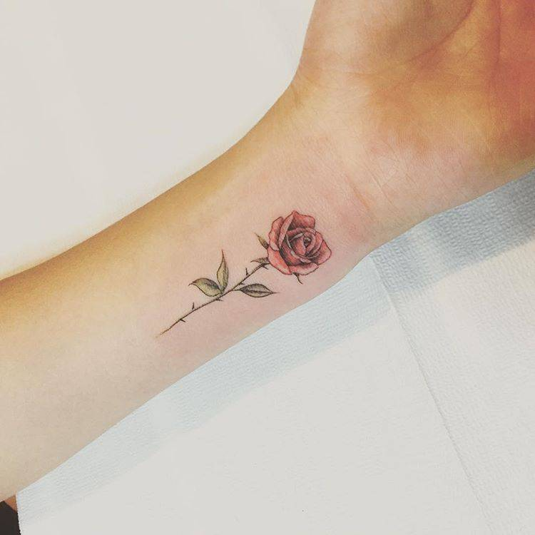 Red rose tattoo on the inner wrist.