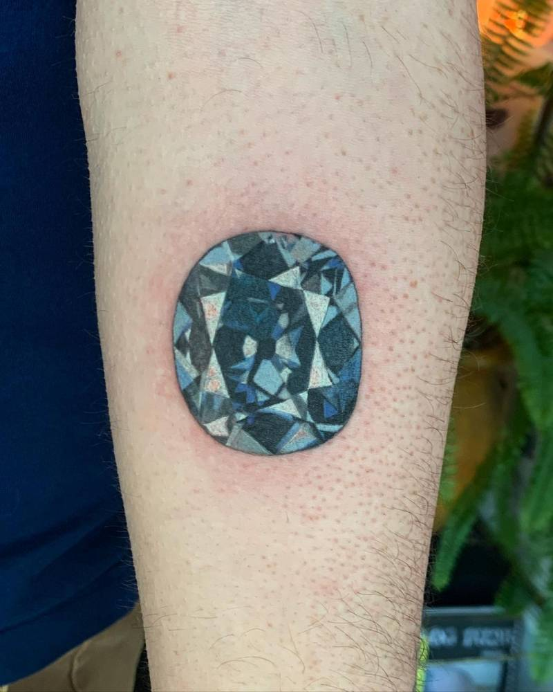 Hope diamond tattoo on the inner forearm.