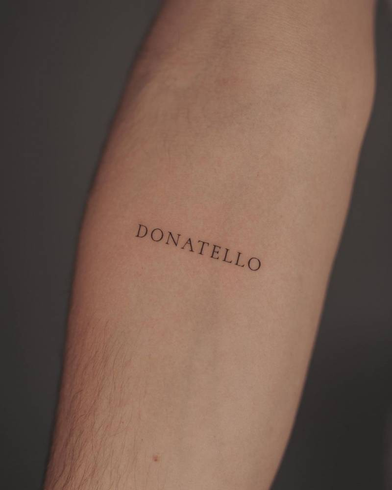 """Donatello"" lettering tattoo on the inner forearm."