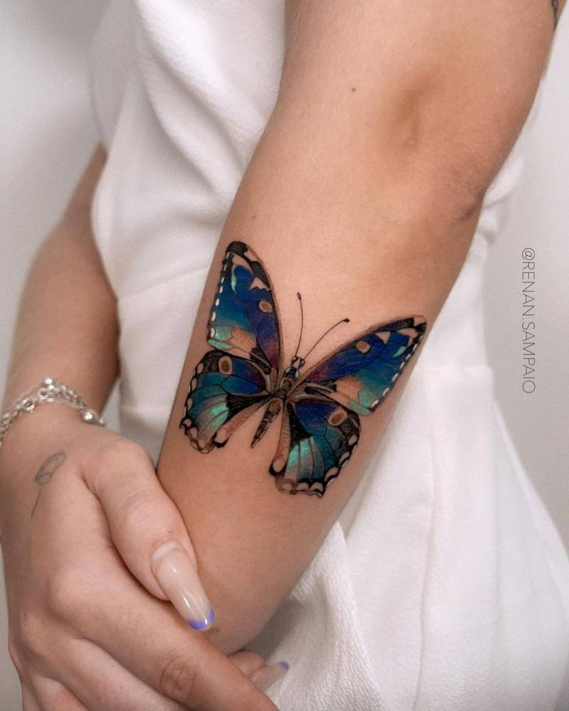 Blue butterfly tattoo on the forearm.