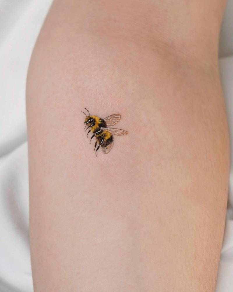 Micro-realistic bee tattoo on the inner forearm.