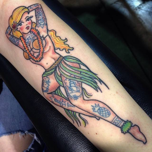 Traditional style hula dancer tattoo on the inner forearm.