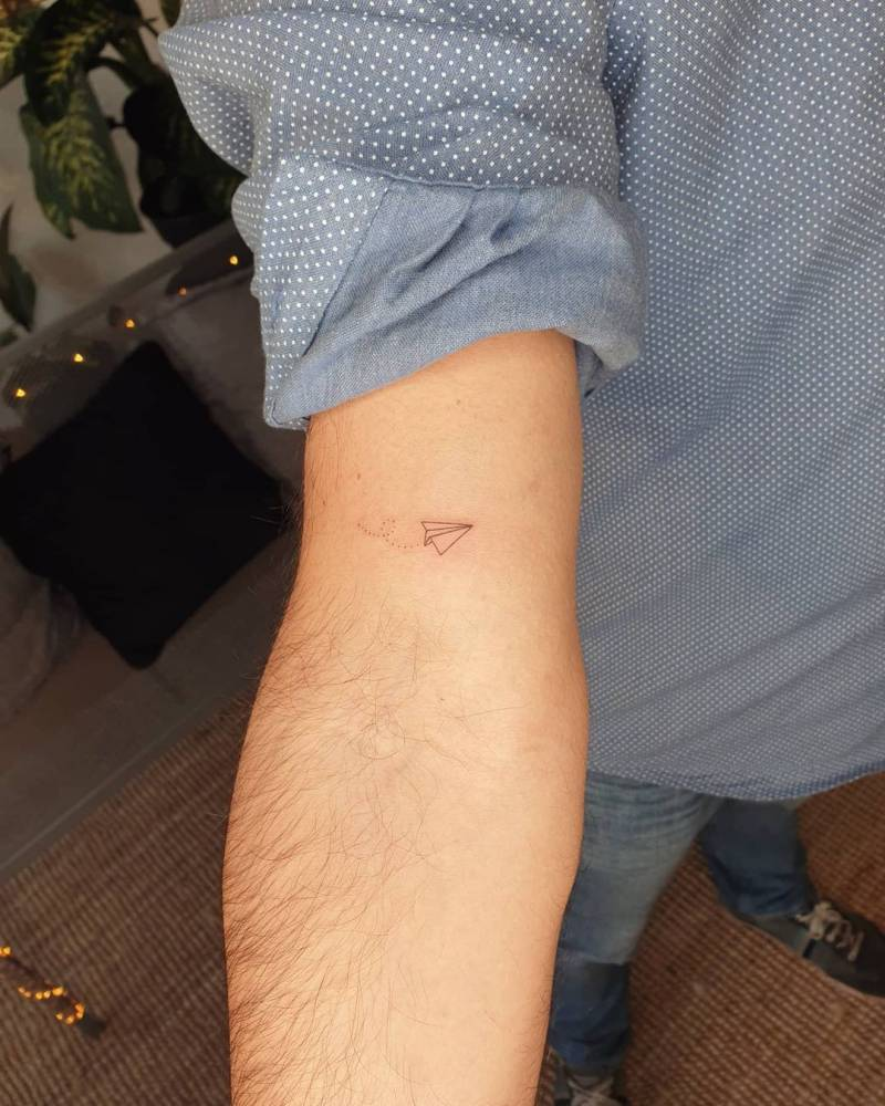 Minimalist paper airplane tattoo on the bicep.