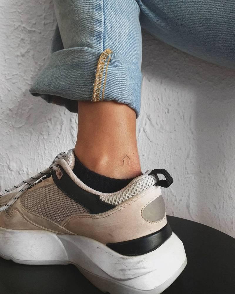 Minimalist tiny house tattoo on the ankle.