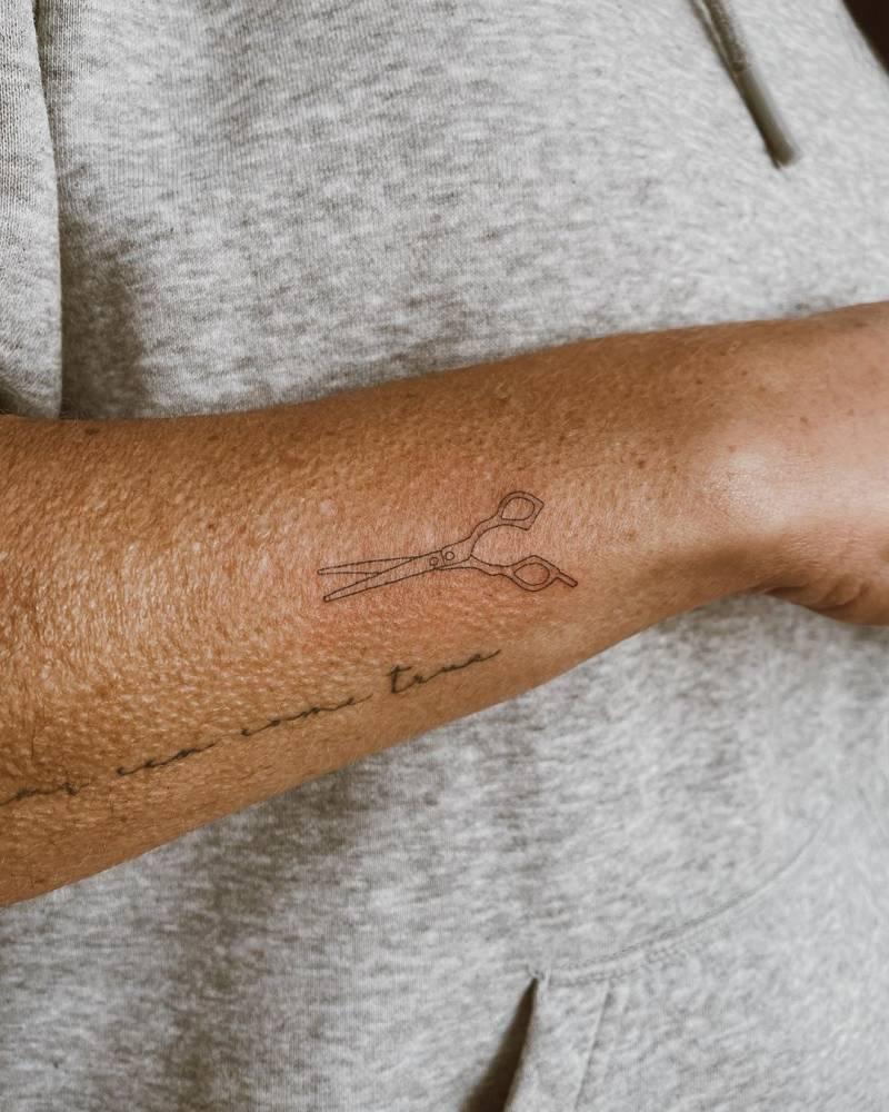 Fine line scissors tattoo on the wrist.