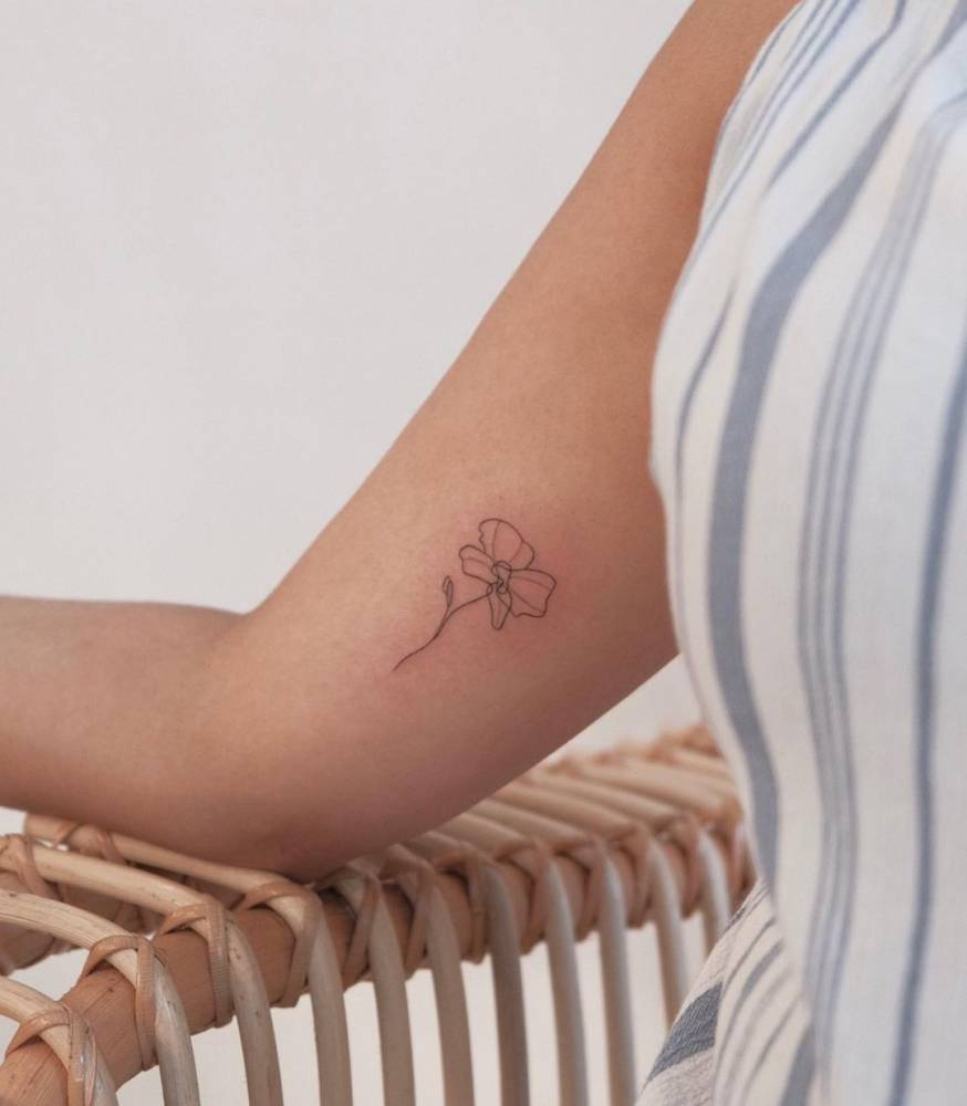 Fine line orchid tattoo on the inner arm.