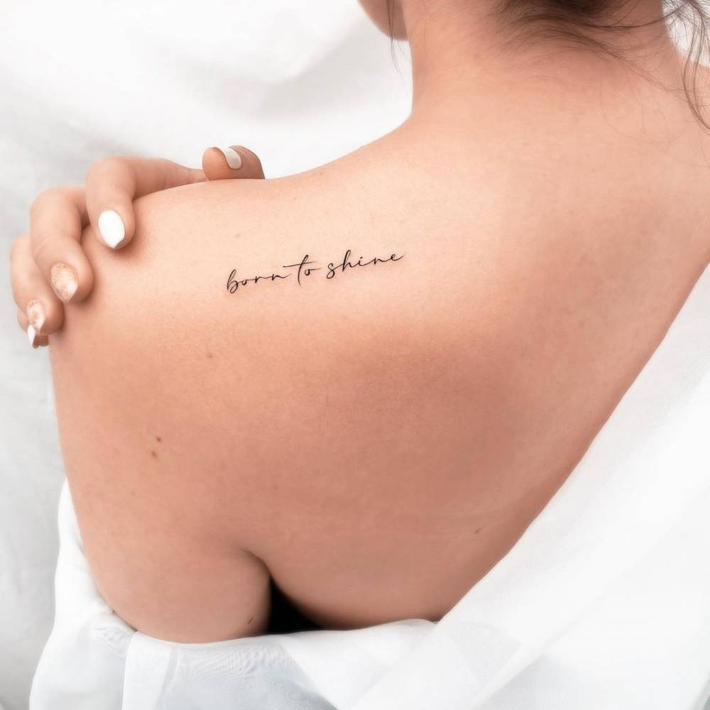 """""""Born to shine"""" lettering tattoo on the shoulder blade."""