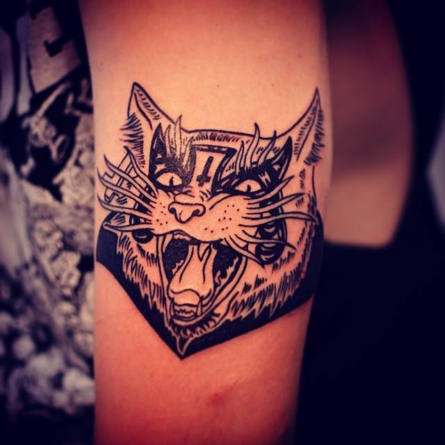 Blackwork cat portrait tattoo on the upper arm.