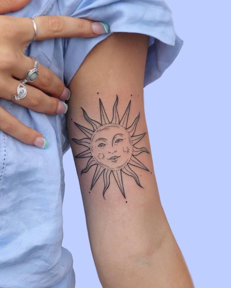 Line art sun tattoo on the inner arm.
