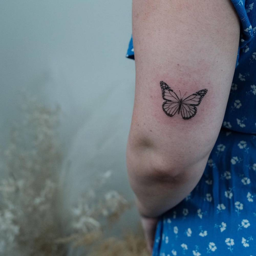 Butterfly tattoo on the tricep.